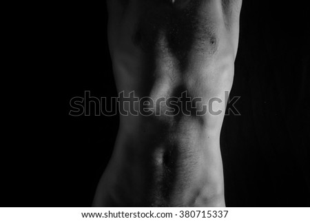 Naked torso of young man on black background
