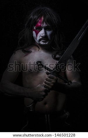 naked warrior carrying steel sword, red face - stock photo