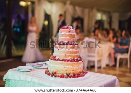 naked wedding cake decorated with fruits such blueberries and strawberries costs on a plate and couple on background