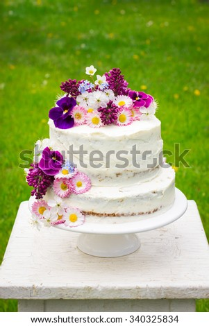 naked wedding cake decorated with spring flowers, selective focus