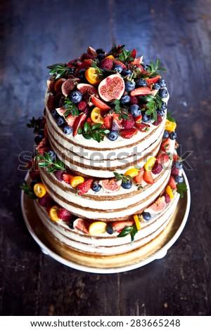 Naked wedding carrot cake with fruits - stock photo