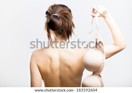 Naked woman back view holding bra in her hand - stock photo