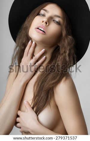 Naked woman in a hat on a gray background