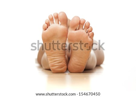 naked woman lying on the floor with a focus on feet - stock photo