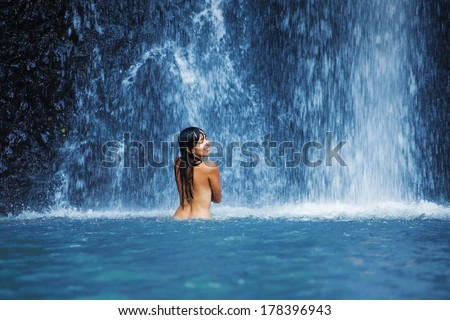 Naked woman washing in waterfall