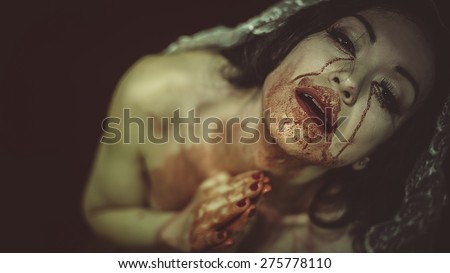 naked woman with blood on her face - stock photo