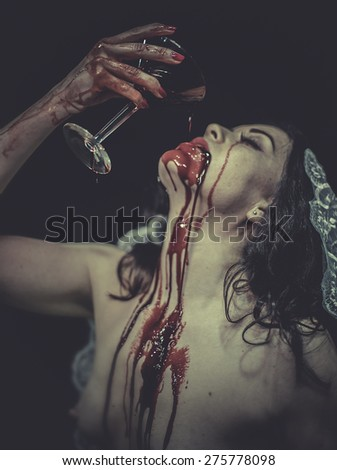 naked woman with blood on his face drinking from a cup, vampire - stock photo