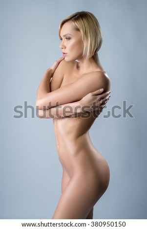 Naked woman with perfect body hugging herself - stock photo