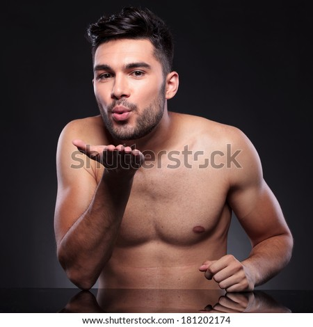 naked young man behind a desk is sending you a kiss through the air. on a black studio backgroud - stock photo