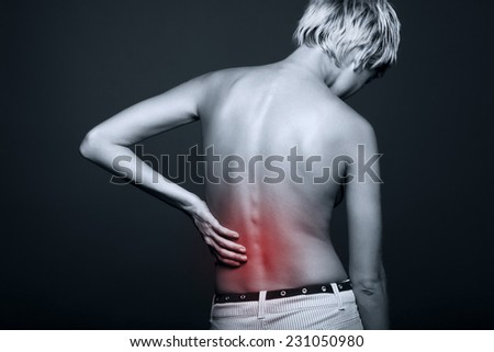 naked young woman with a pain in a waist on a black background.   - stock photo