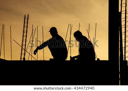 Nakhon Pathom, Kingdom of Thailand - June 2, 2016: Construction workers take a break time, relax and sit down on the beams of the building with sunset in background