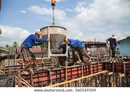 NAKHON RATCHASIMA -DEC 28: Construction workers pouring cement to creating beam to build a house on December 28, 2015 in Nakhon Ratchasima, Thailand