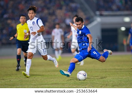 NAKHON RATCHASIMA THA-Feb07:Kroekrit Thaweekarn#4 of Thailand drives a ball during the 43rd King's cup match between Thailand and Korea Rep at Nakhon Ratchasima stadium on February07,2015 in Thailand. - stock photo