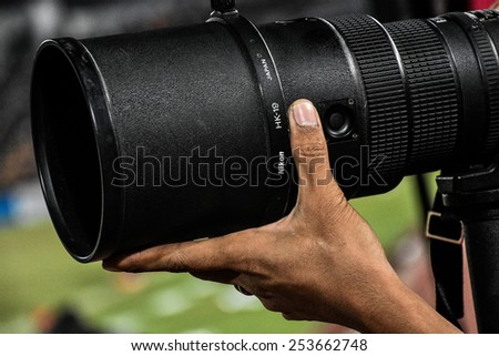 NAKHON RATCHASIMA THA-Feb07:Photographer  with big zoom digital lens during the 43rd King's cup match between Thailand and Korea Rep at Nakhon Ratchasima stadium on February07,2015 in Thailand - stock photo