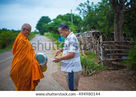 Nakhon Ratchasima, Thailand. October 7, 2016: An unidentified man feeding monk.Thai with Aboriginal people to make merit by offering food to the monks. Nakhon Ratchasima. Thailand.