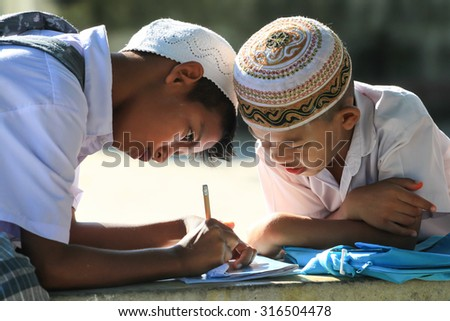 NAKHON SI THAMMARAT THAILAND- JUNE 12: Unidentified Islamic students teaching each other while waiting for classroom  on June 12, 2010 at Panya Saratham Moonithi School , Nakhon Si Thammarat Thailand. - stock photo