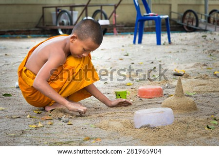Nakhon Sri Thammarat, THAILAND - APR 14, 2015: Young monk playing sand at temple on Songkran's Day.