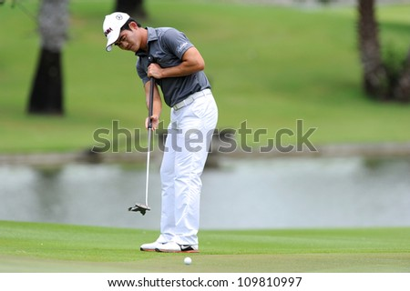 NAKHONPATHOM,THAILA ND - AUG 9:Liang Wen-chong of CHN  watches the ball after a put shot during day one of the Golf Thailand Open at Suwan Golf&Country Club on August 9, 2012 in Nakhonpathom Thailand