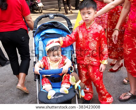NAKHONSAWAN/THAILAND-FEBRUARY 11, 2016: Procession of Chinese New Year Festival at hundred anniversary year on streets in the city. Boy and baby waiting to see the procession with their parents.