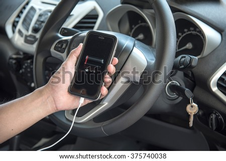 NAKORN PATHOM, THAILAND - FEB 12, 2016: A man hand holding screen shot of battery dead showing on iPhone 6 in the car. - stock photo