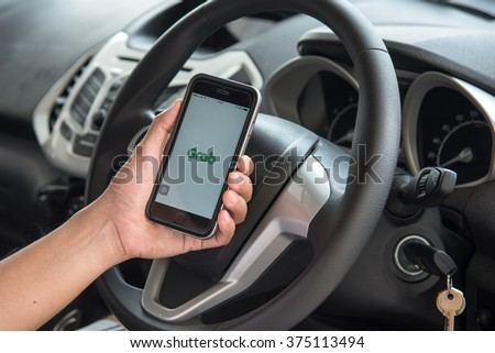 NAKORN PATHOM, THAILAND - FEB 11, 2016: A man hand holding screen shot of Grab Taxi app showing on iPhone 6 in the car. - stock photo