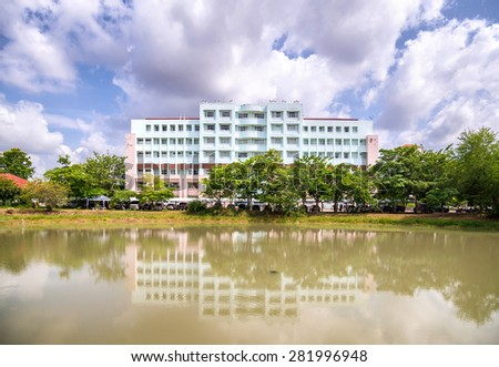 Nakornnayok , Thailand May 10 , 2015 : Reflection of building with cloudy sky - stock photo
