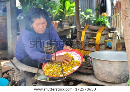 NAKORNRAJASIMA< THAILAND - SEP 23: Unidentified woman boil silk worm for on September 23, 2012 in Lhung Pra Doo Village, Nakornrajasima, Thailand. Famous village about silk woven. - stock photo