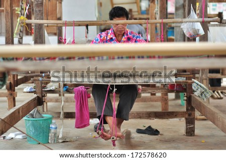 NAKORNRAJASIMA< THAILAND - SEP 23: Unidentified woman weave woven on September 23, 2012 in Lhung Pra Doo Village, Nakornrajasima, Thailand. Famous village about silk woven. - stock photo