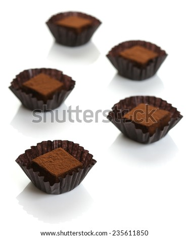 Nama Chocolate (also called raw chocolate) is a modern Japanese confectionery of plain ganache (chocolate mixed with heavy cream and liqueur), covered with cacao powder. Served in glassine candy cups. - stock photo