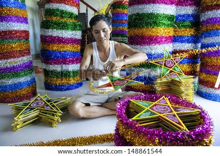 NAMDINH - AUGUST 4: A craftsman making the star lanterns. Photo taken in Namdinh - Vietnam in august 4, 2013. The star-shaped lanterns, a specific kind of toys for Mid Autumn Festival in Vietnam. - stock photo