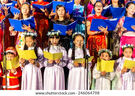 NAMDINH CITY, VIETNAM - DECEMBER 24, 2014 - Christian believers singing a Christmas carol on Christmas Eve in front of the Grand Cathedral. Namdinh is also famous for religious openings. - stock photo
