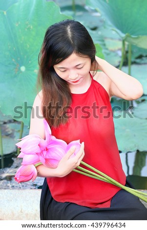 NAMDINH, VIETNAM June 12, 2016: Girl dressed in ethnic picking in lotus lagoon. Lotus is the national flower of Vietnam considered.