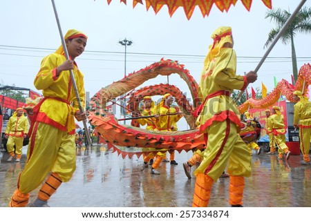 NAMDINH, VIETNAM - MARCH 02: A group of unidentified dancer with their colorful dragon during the traditional festival celebrations in the Tet Lunar New Year on March 02, 2015 in Nam Dinh, Vietnam. - stock photo