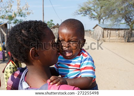 NAMIBIA, KAVANGO, OCTOBER 15: Unidentified Namibian mother carries her baby in her arms.. Kavango region near Rundu. October 15, 2014, Namibia - stock photo