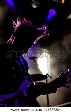 NAMPA, IDAHO - SEPTEMBER 25 : Eric Bass from Shinedown plays bass against a backlight at the Rockstar Uproar Festival on September 25, 2012 in Nampa, Idaho.