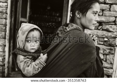 NAMRUNG, NEPAL - October 21: Unidentified Nepali woman carries a child on her back in a sack. October 21, 2015 in Namrung.