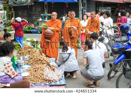 NAN THAILAND - OCTOBER 19 : Tourists and locals give alms food to monks during the morning on October 19,2014 in Nan,Thailand. - stock photo