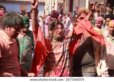 NANDGAON - FEB 28: Devotees throw colors and dance during the Holi celebration at Krishna temple on February 28, 2015 in Nandgaon, India. Holi is the most celebrated religious festival in India. - stock photo
