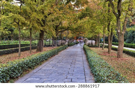 Nanjing MIng Dynasty tomb of chinese emperor garden alley with mystical creatures along the path way under green yellow autumn trees