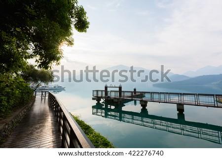 Nantou, Taiwan - May 09, 2016 : Tourist boats docking and sidewalk in peachful morning at Shuishe Pier, Sun Moon Lake, Taiwan. - stock photo