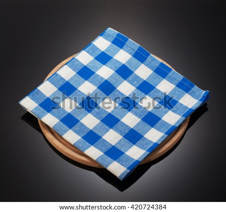 napkin cloth and cutting board on black background - stock photo