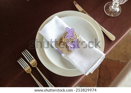 napkin decorated with two violet butterflies and twine tied in a bow - stock photo