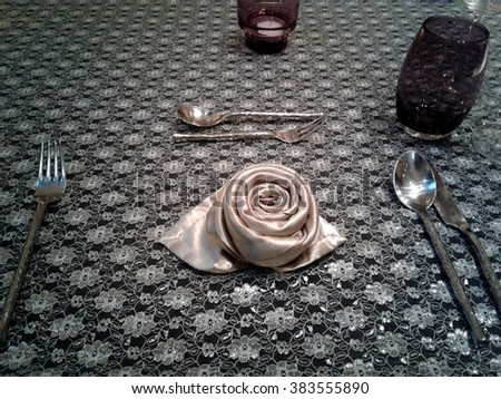 Napkin folded as a rose on the dinner table - stock photo