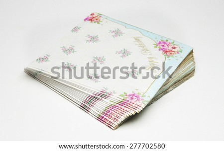 napkins with flowers as decoration and happy birthday in white background - stock photo
