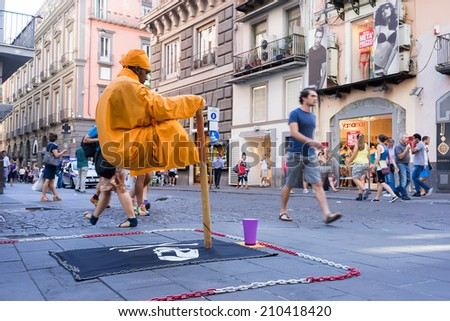 NAPLES, ITALY- AUGUST 3, 2014: Street performer in Naples, Italy. Every day, street performers try their hand at making a living from tips on Naples, Italy.  - stock photo