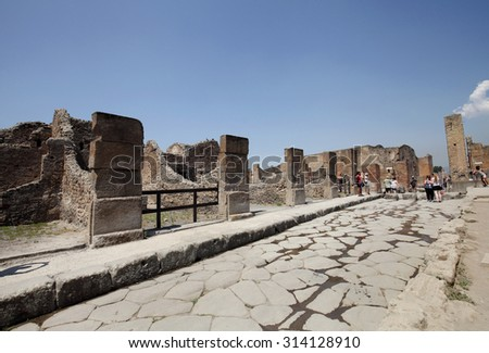 NAPLES, ITALY - JULY 17: Tourists visit the excavated ruins of Pompeii city on July 17, 2015, Naples, Italy. The city was buried under ash and debris during the eruption of Mount Vesuvius in 79 AD