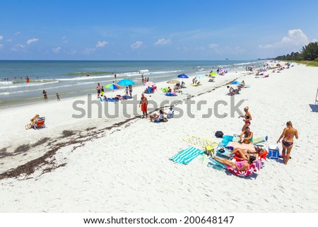 NAPLES, USA - JULY 27, 2013: people enjoy the beautiful public white beac  in Naples, USA. The beach is lively and is lined with some of Naples' most luxurious homes, many visible from atop the pier
