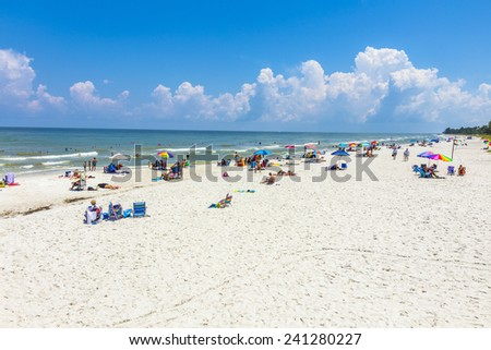 NAPLES, USA - JULY 27, 2013: people enjoy the beautiful public white beach at Naples Pier in Naples, USA. The beach is lined with some of Naples' most luxurious homes, many visible from atop the pier