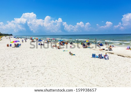 NAPLES, USA - JULY 27: people enjoy the beautiful public white beach at Naples Pier on July 27, 2013 in Naples, USA. The beach is lively and   lined with some of Naples' most luxurious homes.