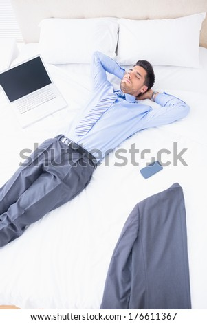 Napping businessman lying on his bed at home in bedroom